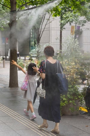Pedestrians in Tokyo walk under cooling water sprays.