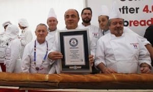 French and Italian bakers pose with the longest baguette in the world.