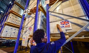 Beverley Sarpong placing UK aid stickers onto cargo pallets containing British aid items, 2014
