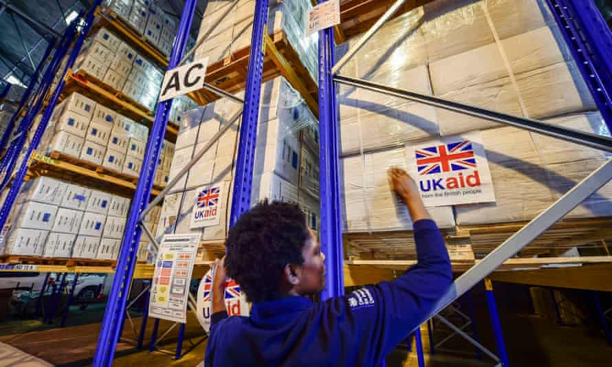 A logistics officer places UK aid stickers on to cargo pallets at DfID's UK Disaster Response Operations Centre in Kemble.