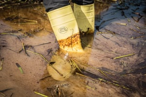 Person wearing wellington boots in oily water in Bayelsa, Nigeria, 8 June 2018