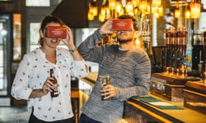 woman and man drinking beer, wearing VR headsets