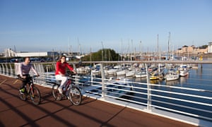 Cyclists on bridge over part of Cardiff Bay moorings, Wales, UK