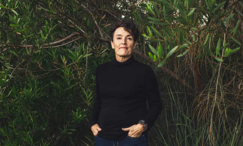Edwina Robinsons wears a black top and jeans in front of tall, thick green plants