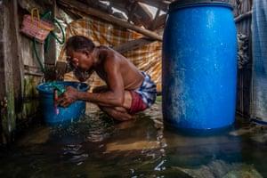 Rozikin washes inside his flooded bathroom.