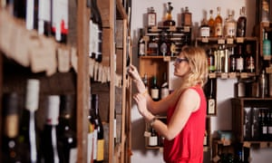 Side view of female business owner examining wine bottles at shop