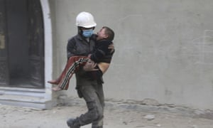In this photo released on Wednesday Feb. 21, 2018, provided by the Syrian Civil Defense group known as the White Helmets, shows a member of the Syrian Civil Defense group carries a boy who was wounded during airstrikes and shelling by Syrian government forces, in Ghouta, a suburb of Damascus, Syria. New airstrikes and shelling on the besieged, rebel-held suburbs of the Syrian capital killed at least 10 people on Wednesday, a rescue organization and a monitoring group said. (Syrian Civil Defense White Helmets via AP)