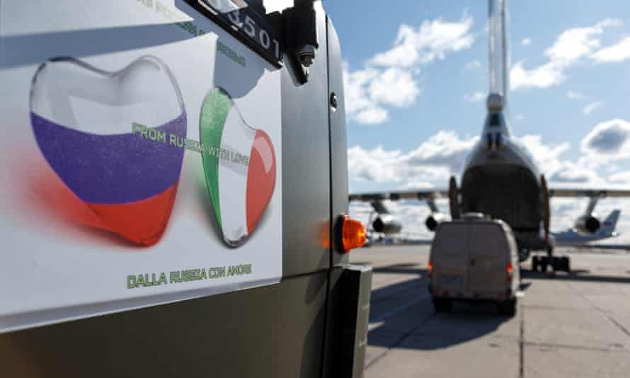 The side of a truck bearing Russian and Italian flags in the shape of love hearts next to a military plane being loaded with aid supplies