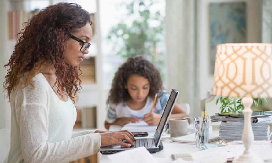 Woman using laptop at home, girl (8-9) doing homework in background