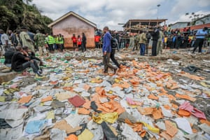 Nairobi, Kenya: People walk on the pages from text books strewn on the ground where the school building stood before collapsing near Kawangware slum