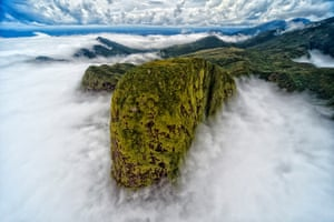 A top of a mountain rage surrounded by clouds