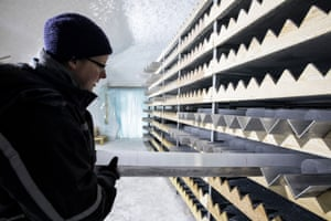 In the storage cave, a scientist handles an ice core containing volcanic ash.