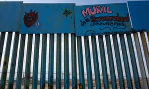 A section of the US-Mexico border fence painted with murals.