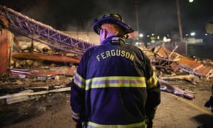 A Ferguson firefighter surveys rubble at a strip mall that was set on fire when rioting erupted following the grand jury announcement in the Michael Brown case