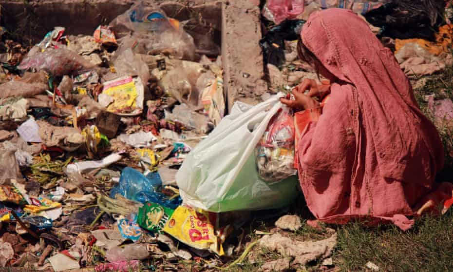 Eight-year old Zarmeena collecting rubbish from pile in Islamabad.