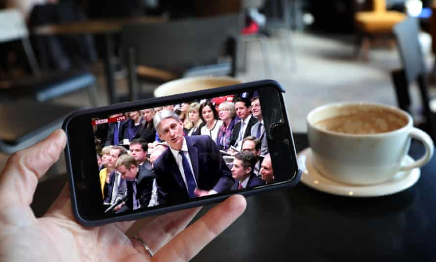 A smartphone user watches Philip Hammond deliver his budget speech