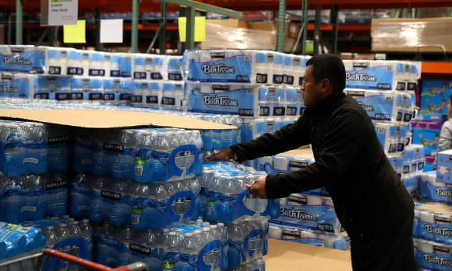 A customer grabs a case of drinking water at a Costco store on 14 March 2020 in Novato, California.