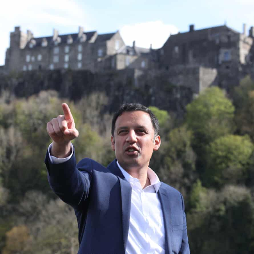 Anas Sarwar pointing as he speaks outdoors, with  Stirling Castle at the top of the hill behind him