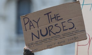 "A cardboard sign being held aloft reads ""Pay the nurses"" followed by a list of auxilary health professionals (midwives, occupational therapists, etc.), and the line ""also - don't bomb Syria""."