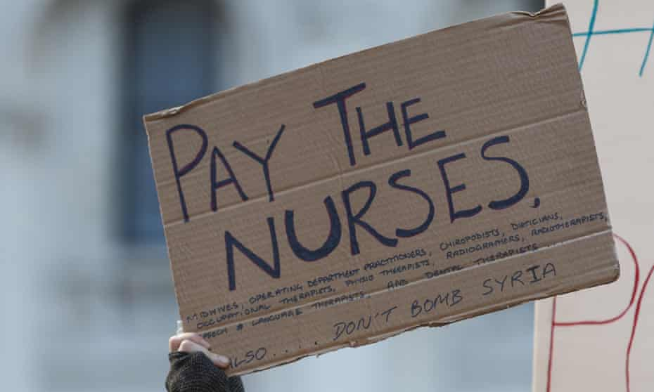 Paper sign saying 'Pay the nurses' held in air during protest at government's proposal