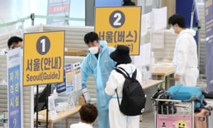 Arriving passengers are guided by quarantine officials at Incheon International Airport, South Korea.