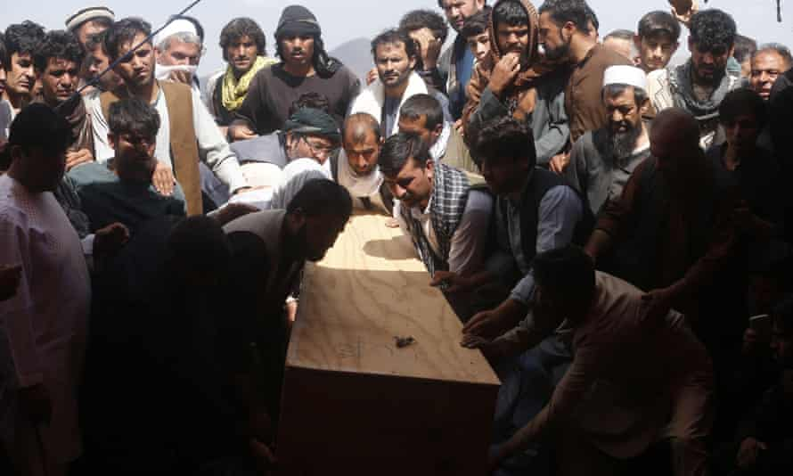 Afghans carry the body of a victim of the Dubai City wedding hall bombing during a mass funeral.