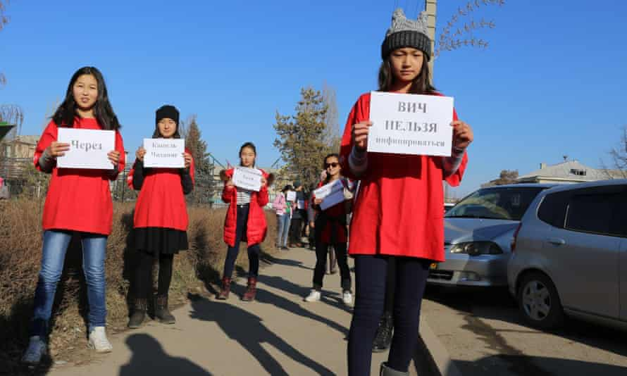 Volunteers in Kyrgyzstan raise awareness about HIV/Aids by holding signs explaining how HIV can and cannot be transmitted.
