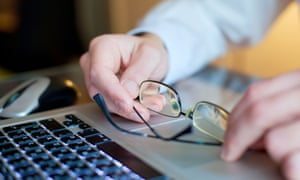 A man's hands and glasses on a laptop