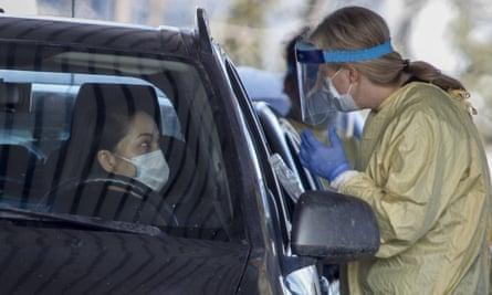 An Alberta health services employee speaks with a motorist at a drive-thru coronavirus testing facility in Calgary, Alberta.