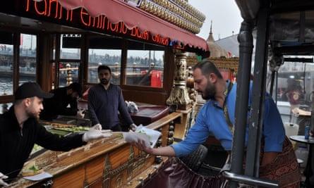 A waiter passes a fish sandwich from a balık ekmek boat in Istanbul's Eminönü district.