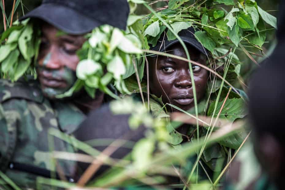 A female Gabon national park ranger sits with other rangers in the dense undergrowth of a rainforest.