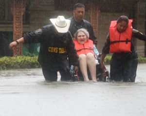 Precinct 6 Deputy Constables Sgt. Paul Fernandez, from left, Sgt. Michael Tran and Sgt. Radha Patel rescue an elderly woman from rising water on North MacGregor Way, near Brays Bayou, after heavy rains from the remnants of Hurricane Harvey