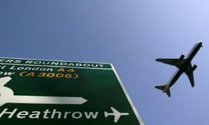 A plane flies above a Heathrow road sign