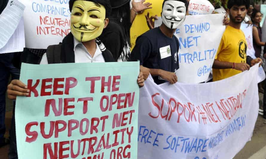 Activists wear Guy Fawkes masks as they hold placards during a demonstration supporting net neutrality in Bangalore