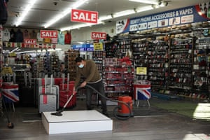 A man hoovers as a souvenir shop reopens in London.