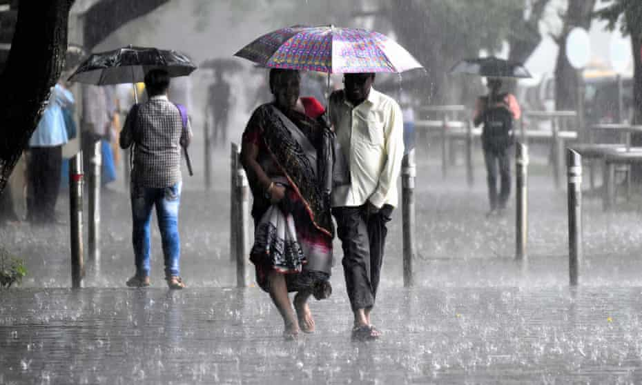 Commuters cover themselves under umbrellas after a sudden rain shower at St Xavier's College in Mumbai, India.