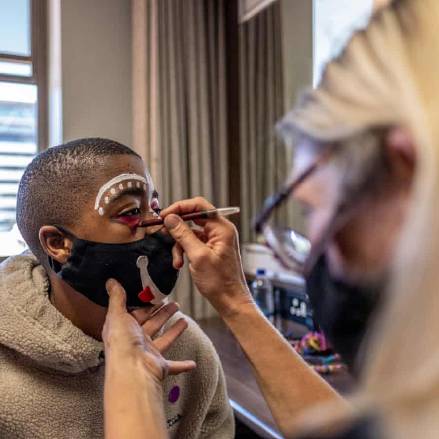 Ayabonga Tshofui, a College of Magic student, has his face painted before a performance at the Artscape theatre centre.