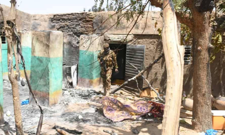 A soldier walks amid damage after an attack by gunmen in Ogossagou, Mali. Increasing intercommunal violence and the presence of armed groups has resulted in repeated attacks in central Mali.
