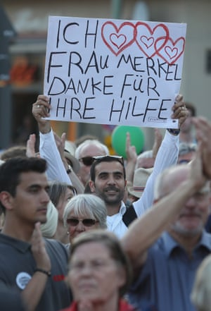 A man claiming to be a Syrian refugee holds up a sign that reads: 'I love Mrs Merkel, thank you for your help' at a CDU campaign rally in Berlin.
