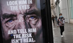 A man wearing a mask walks past an NHS poster about Covid-19 in London