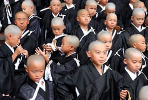 Children with shaven heads and wearing kesa robes attend  a ceremony to become Buddhist monks in Kyoto Japan