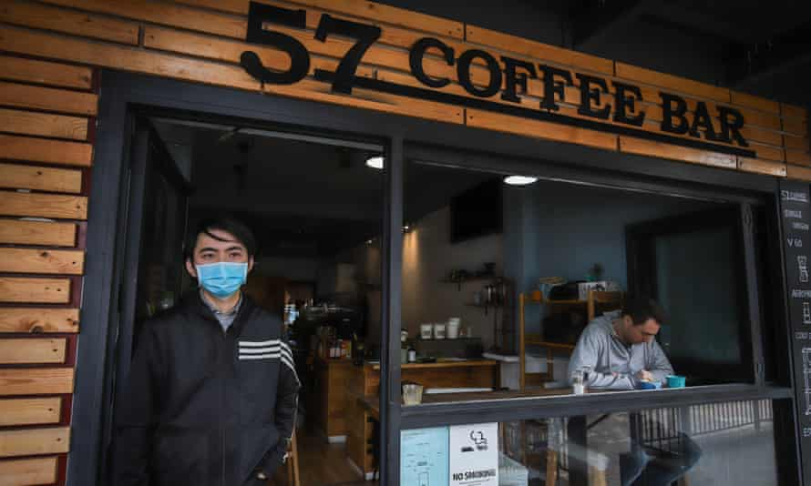 A cafe owner stands outside his premises wearing a face mask as his first customer sits with his coffee in Neutral Bay, Sydney, Australia