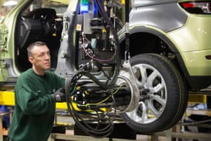 A JLR employee using a robotic arm to fix an alloy wheel to the hub of a Range Rover Evoque SUV.