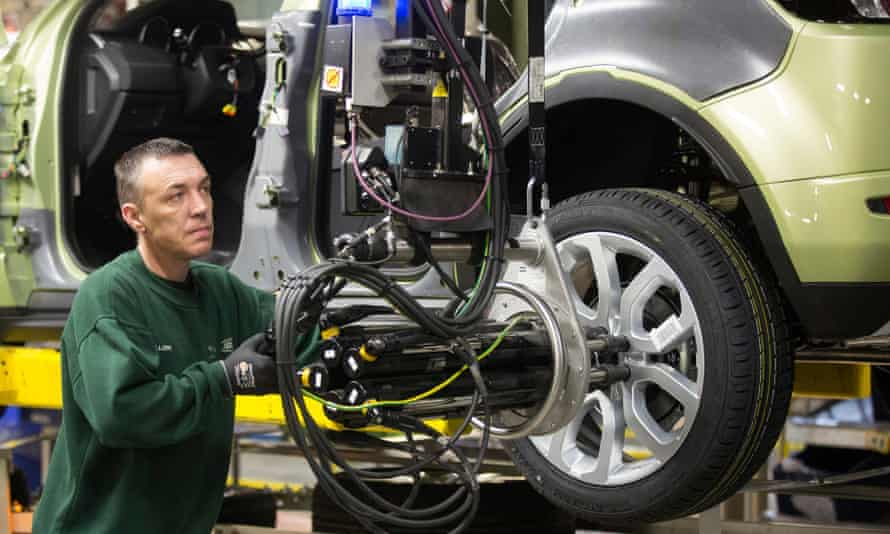 An employee uses a robotic arm to fix an alloy wheel to the hub of a Range Rover Evoque.