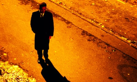 A man stands in a street at night
