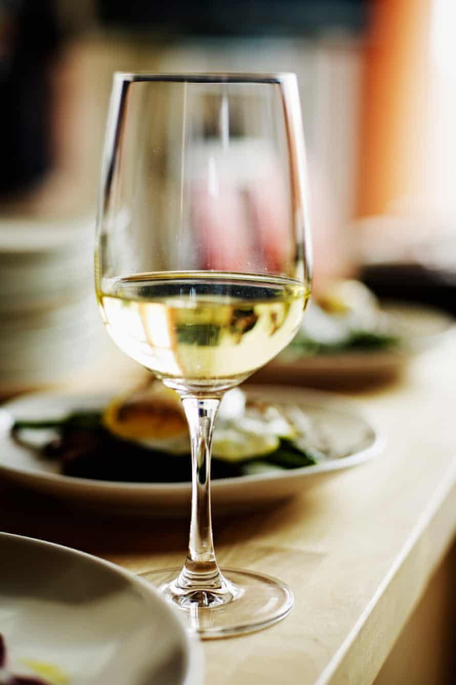 Glass of white wine sitting on countertop with plates of food