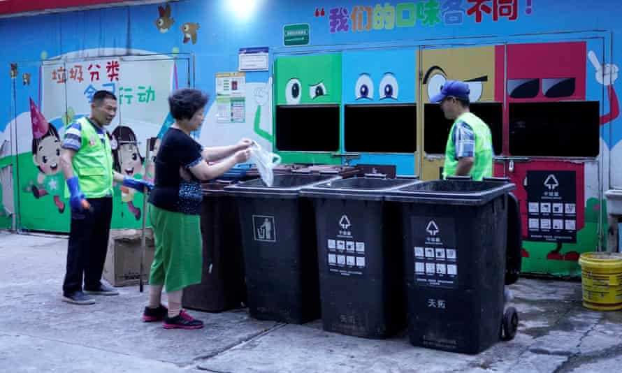 A woman throws at a waste sorting site in Shanghai. Residents face penalties for using the wrong bins.