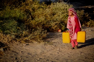 A young girl who fled the fighting with her family carries water home on the outskirts of Kandahar.