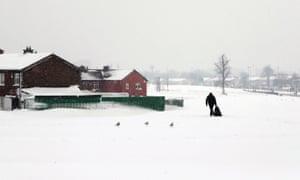 A man drags shopping home through snow in Tallaght, Dublin
