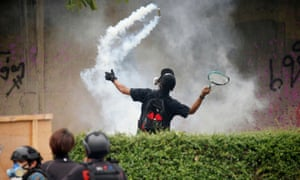 A demonstrator uses a racket against a teargas canister on Friday.